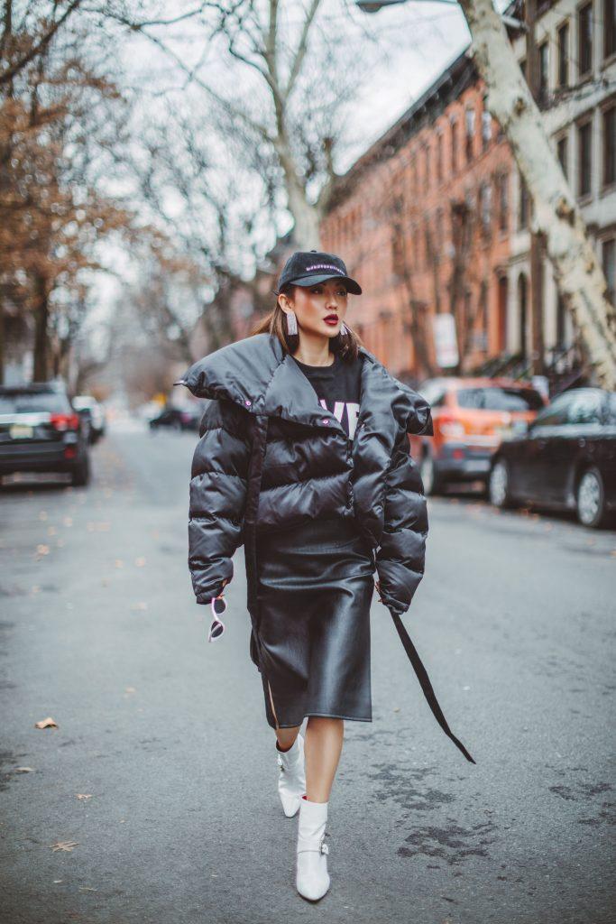 Кожаная юбка до колен и белые ботильоны – отличное дополнение к городскому луку с коротким пуховиком