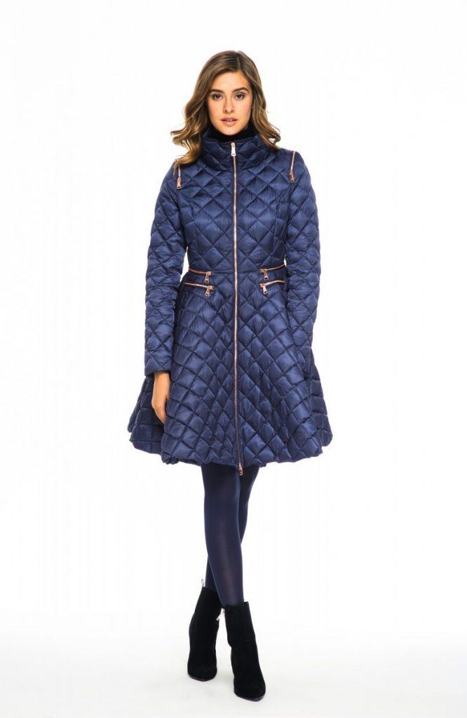 Акцентирует стройность фигуры фасон синего пуховика типа платье в тандеме с бархатной черной обувью и плотными колготками одного с ним оттенка