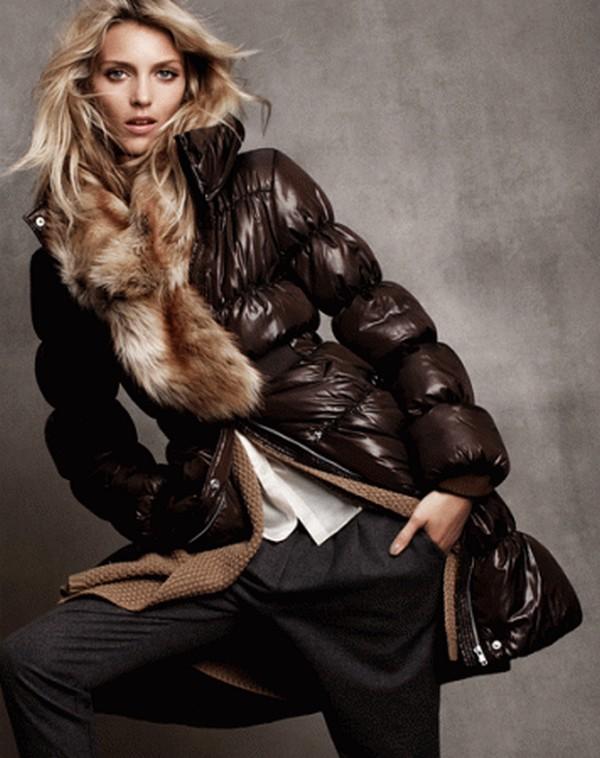 Стильный гламурный лук из блестящего темно-коричневого пуховика с более светлой опушкой и темно-серых брюк прямого кроя