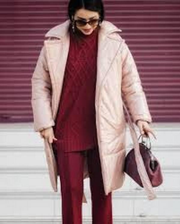 Стильное дополнение к повседневному луку с удлиненным розовым пуховиком – небольшая сумочка в одной цветовой гамме со свитером и брюками