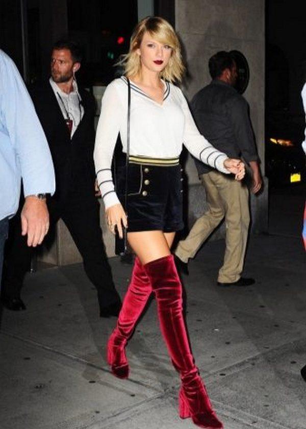 Красные велюровые ботфорты и укороченные черные шорты – в луке акцент намеренно сделан на стройные ноги
