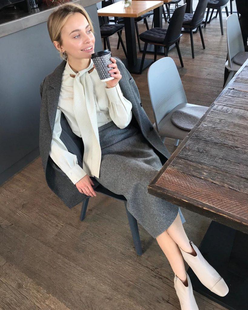 Молочные ботильоны в цвет рубашки отлично дополнят серую юбку карандаш в офисном луке.