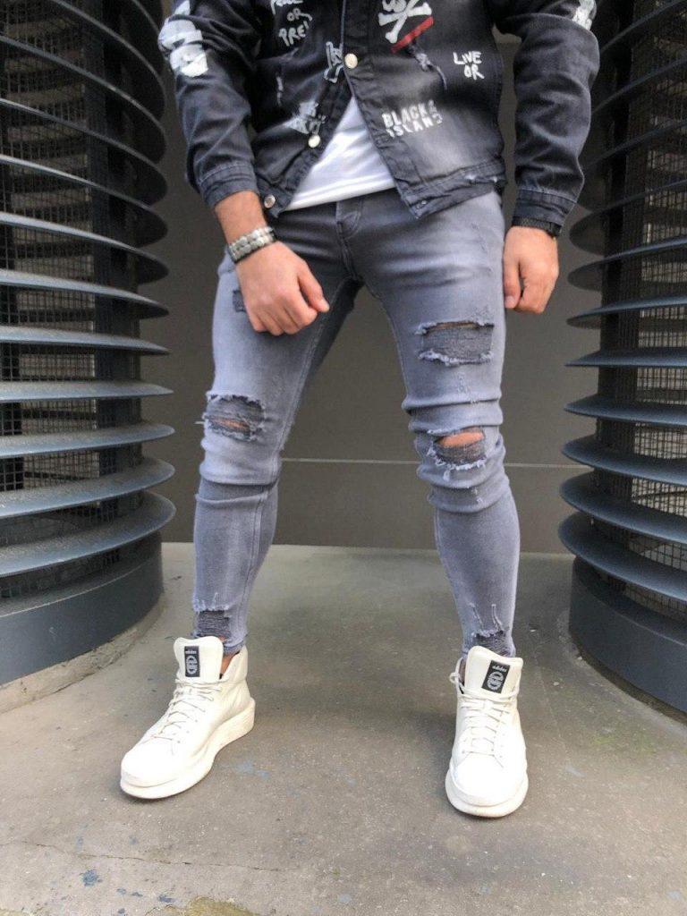 Белые кроссовки в сочетании с рваными серыми джинсами.