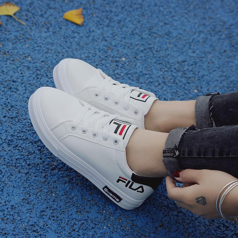 Белые кроссовки на низкое подошве отлично сочетаются с темными джинсами