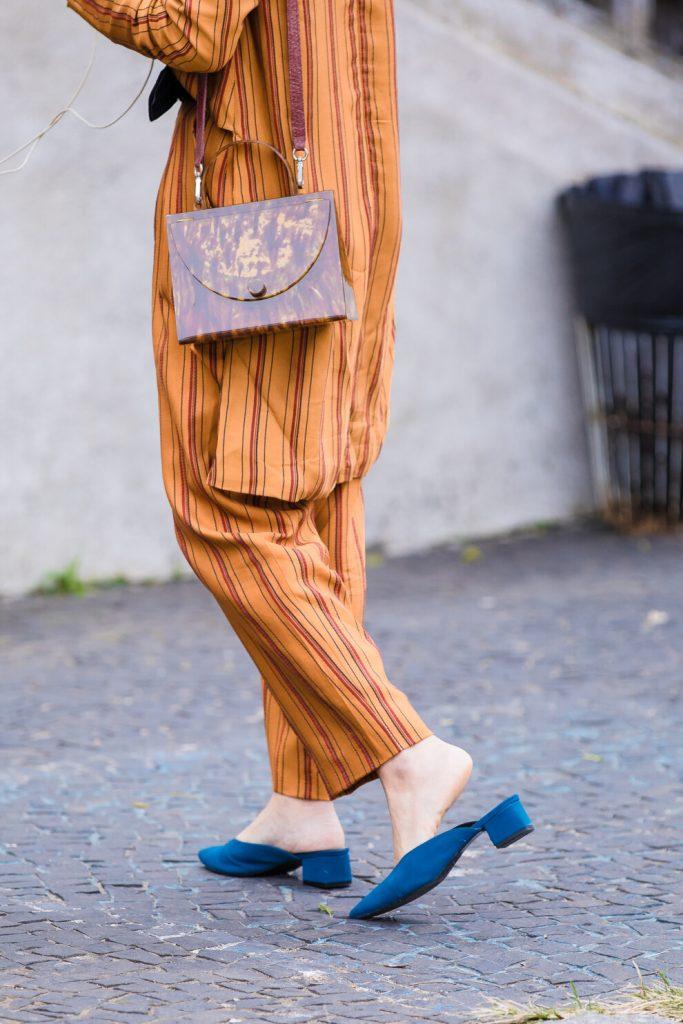 Штаны и рубашка вольного кроя отлично гармонируют с синими мюлями.