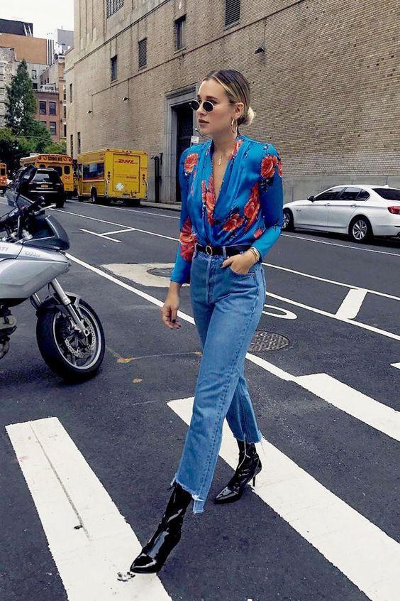 Черные лаковые ботинки, свободные светлые джинсы и шелковая синяя рубашка с принтом в виде роз, можно добавить очки, на данном фото округлой формы.