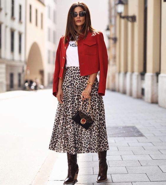 Одна из тенденций - длинная леопардовая юбка, которую нужно комбинировать со спокойным и однотонным верхом. Темно-коричневые лаковые ботинки на низком каблуке отлично дополнят такой образ.