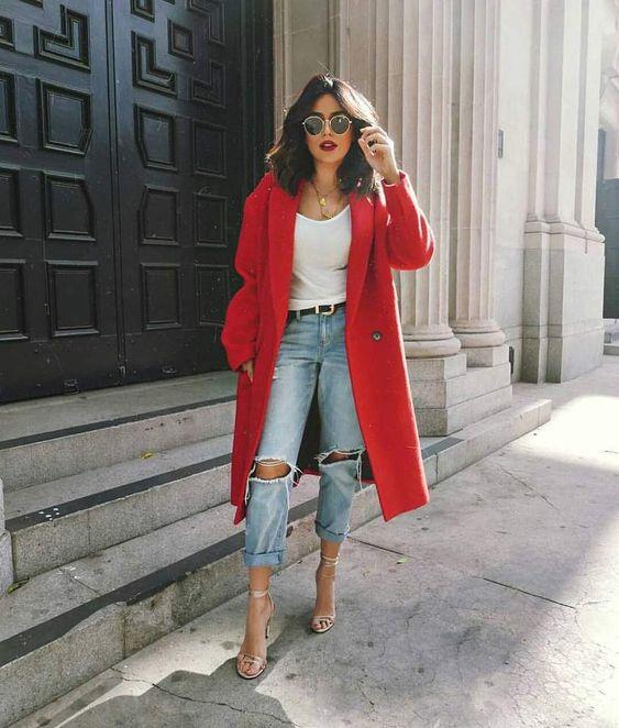 Рваные джинсы-бойфренды, белая майка, красное свободное пальто и босоножки на высоком каблуке с переплатами. Образ дополнен очками.