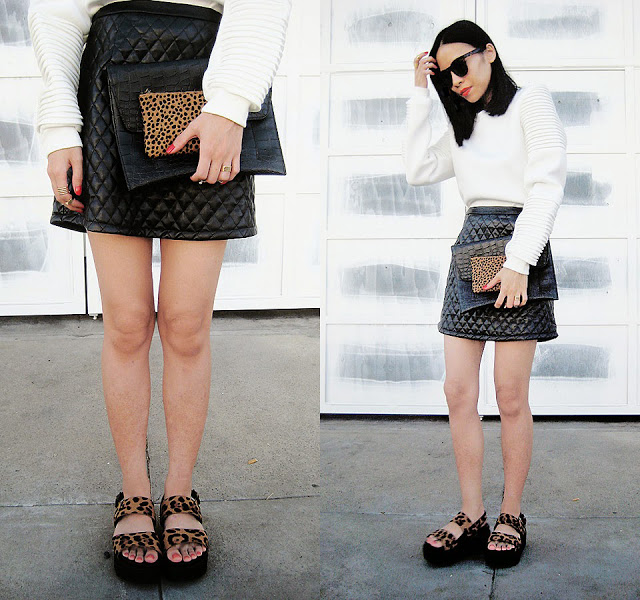 Белый свитер, кожаная черная юбка и босоножки на толстой подошве с леопардовыми вставками.