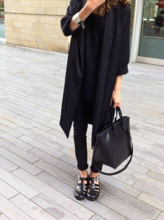 Черная удлиненная футболка и пальто прямого кроя, черные джинсы скинни, большая кожаная сумка и босоножки на толстой подошве с многочисленными ремешками отлично смотрятся вместе.