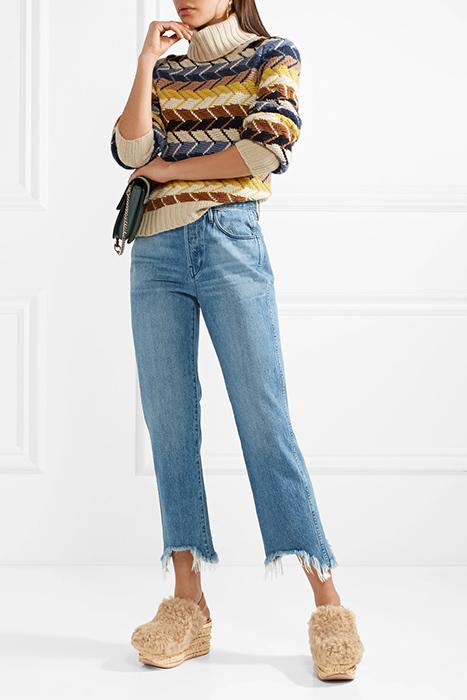 На девушке свитер, прямые синие джинсы и бежевые босоножки на толстой подошве с расширяющейся к пятке подошвой.