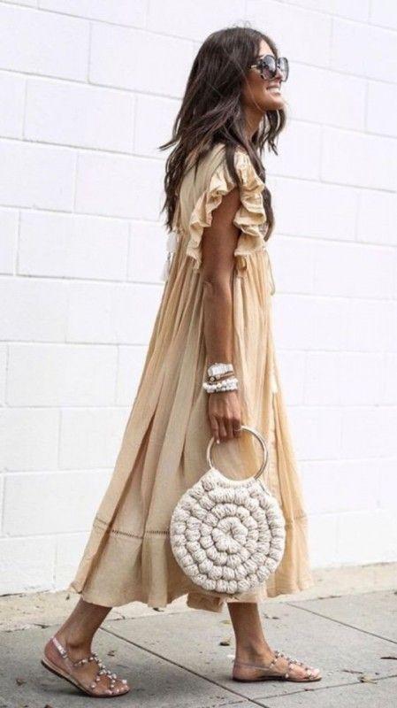 На девушке воздушное бежевое платье макси, босоножки с ремешками и бусинками, белая сумка и очки.