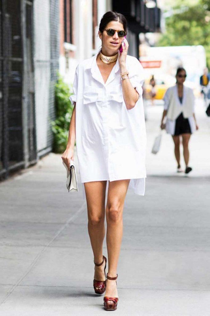 Белое короткое платье-рубашка, белый клатч и кожаные коричневые босоножки на платформе отлично смотрятся вместе. Образ дополнен аксессуарами и очками.
