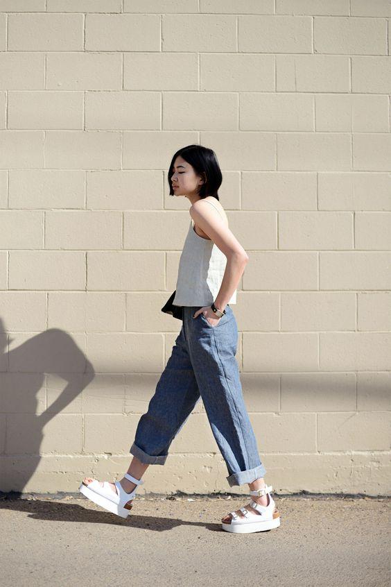 Белая майка, прямые синие джинсы и белые босоножки с ремешками - идеальный повседневный образ.