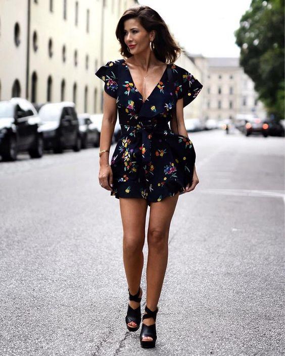 Черное короткое платье на запах с цветочным принтом сочетается с кожаными черными босоножками с завязками вокруг лодыжки.
