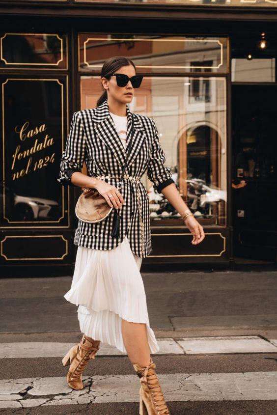 Белая юбка плиссе длины миди, клетчатый удлиненный пиджак, поясная сумка и бежевые замшевые босоножки на толстом каблуке с танкеткой и многочисленными атласными переплатами.
