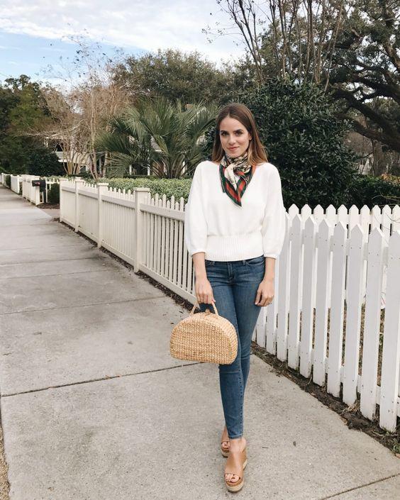 На девушке белый свитер, синие джинсы скинни и нюдовые босоножки на танкетке с открытой пяткой. Образ дополнен веревочной сумкой и шарфом.