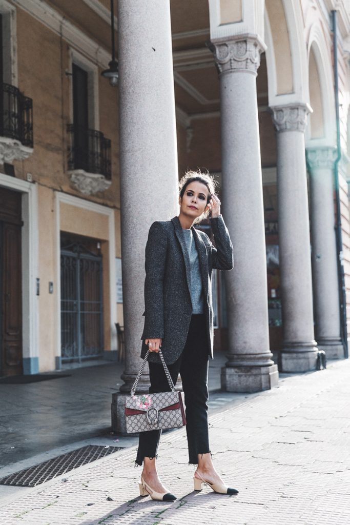 Серая футболка, темно-серый удлиненный пиджак, черный прямые джинсы, сумка и бежевые босоножки на невысоком каблуке с черным носком - удачный повседневный образ.