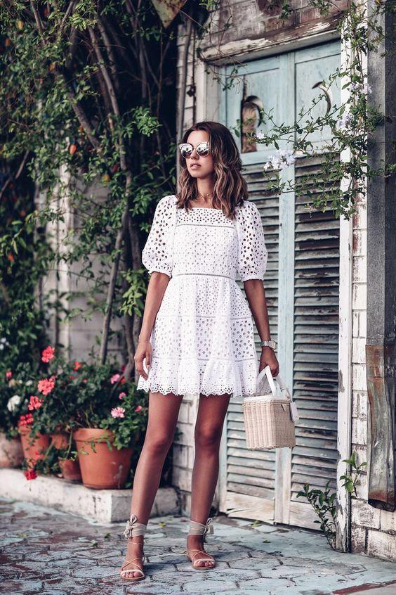 На девушке белое платье шемиз, нюдовые босоножки с веревками и ленточками. Образ дополнен очками и сумкой.