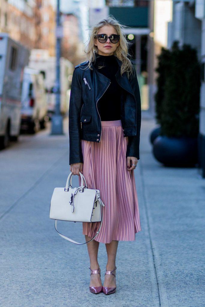 Черная водолазка и кожаная куртка, ярко-розовая юбка плиссе длины миди и розовые босоножки. Образ дополнен очками и белой сумкой.