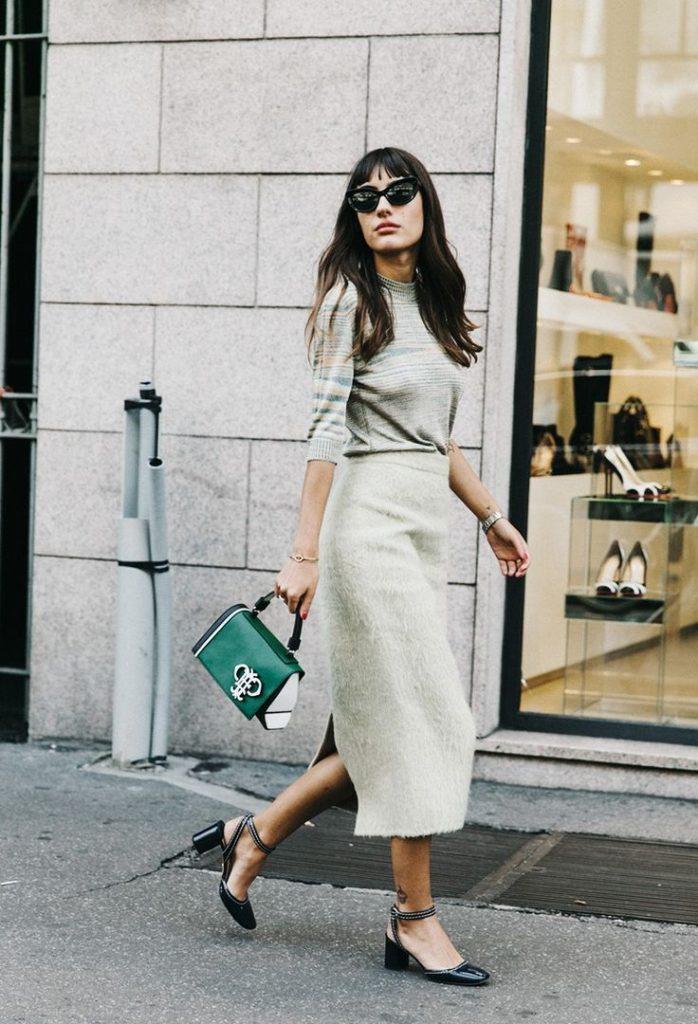 Отличное сочетание - серый свитер, юбка-миди и черные лаковые босоножки с ремешками вокруг лодыжки, зеленая сумка и очки.