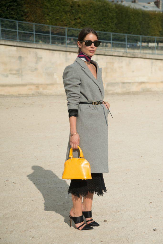 На девушке серое пальто, подчеркнутое ремнем, черное платье-миди и босоножки на шпильке с острым носком, яркая желтая сумка и очки - дополнение к луку.