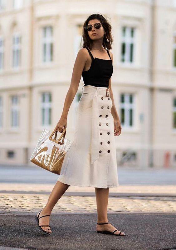 Черная майка, белая юбка ниже колена с пуговицами и простые черные босоножки. Образ дополнен трендовой сумкой и очками.