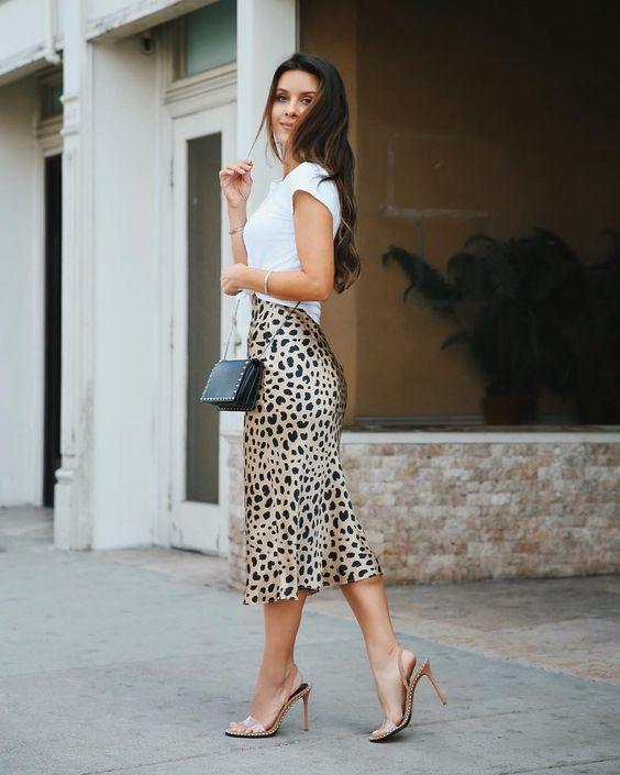 На девушке белая футболка, атласная леопардовая юбка-миди и нюдовые босоножки на каблуке.