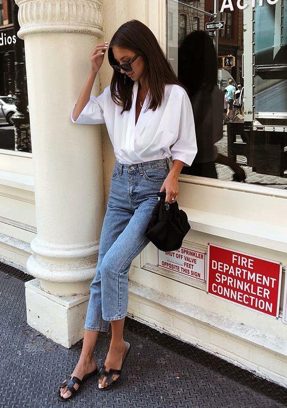 На девушке белая свободная рубашка, прямые голубые джинсы и кожаные черные босоножки на плоском ходу.