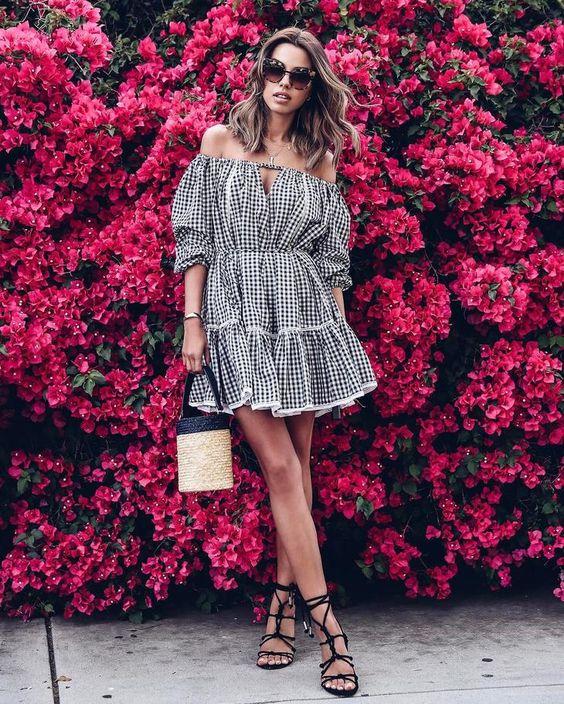 Короткое черно-белое клетчатое платье с воланами, черные босоножки с веревками отлично сочетаются вместе.