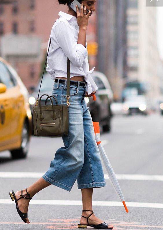 Укороченные джинсовые кюлоты, свободная белая рубашка завязанная на поясе, черные босоножки на низком каблуке и поясная сумка.