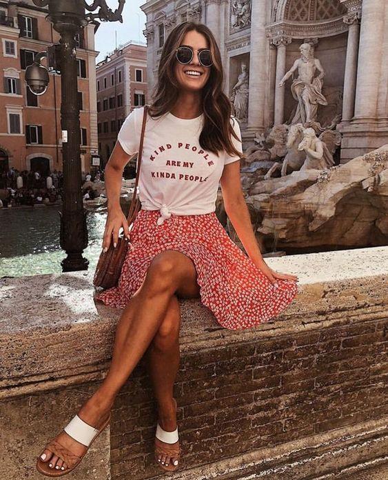 На девушке свободная красная юбка в цветочек, завязанная белая футболка и белые босоножки. Образ дополнен круглой поясной сумкой и очками.