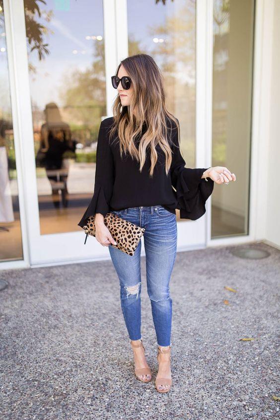 Отлично сочетаются синие джинсы скинни с потертостями, черная блуза с объемными рукавами, бежевые замшевые босоножки на каблуке и леопардовый клатч.