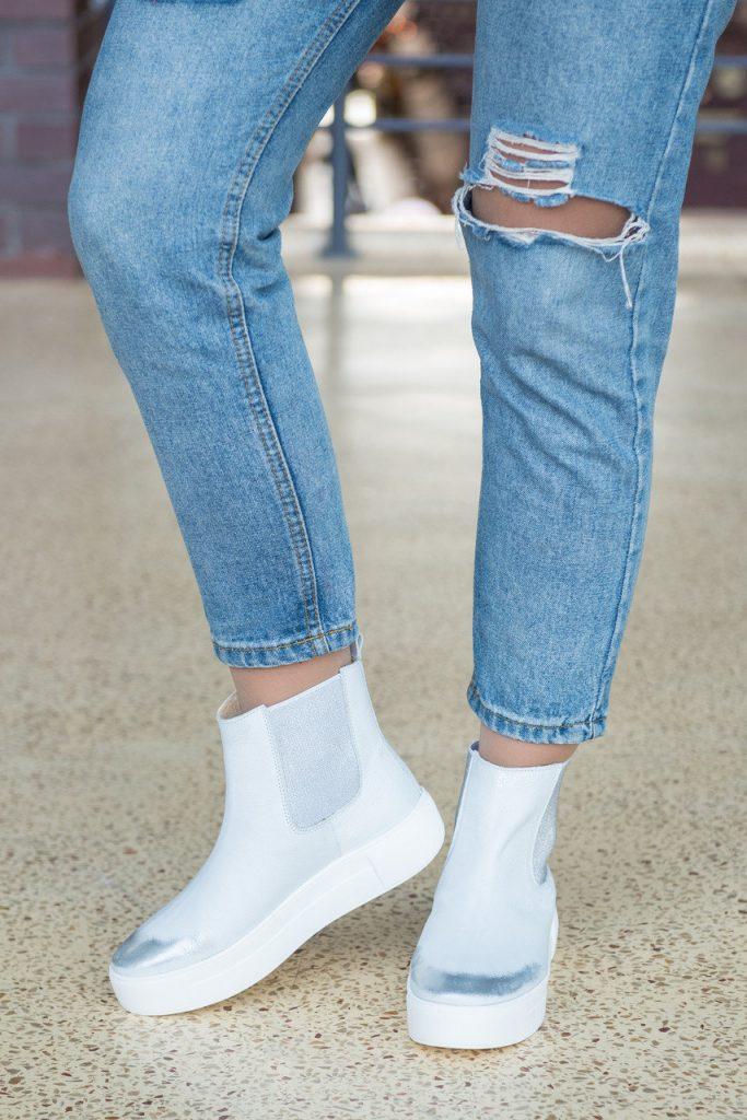 Рваные джинсы и светлые челси создают эффектный, контрастный ансамбль.