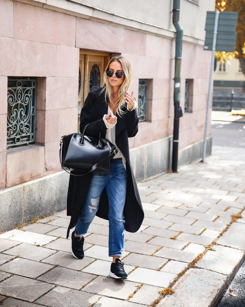 Рваные джинсы с черными кроссовками смотрятся стильно и в меру вызывающе.