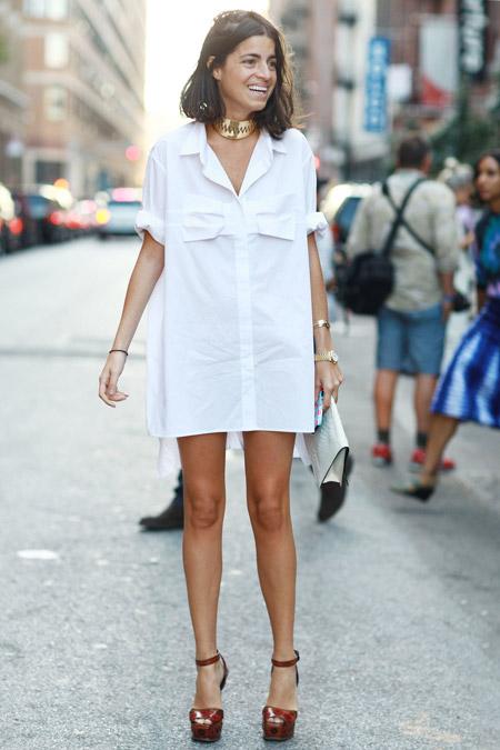 Короткое платье-рубашка белого цвета хорошо сочетается с коричневыми лаковыми босоножками на устойчивом каблуке. В образ добавили аксессуары и белый клатч.