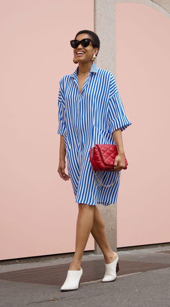 Свободное платье-рубашка в голубую полоску удачно сочетается с белыми туфлями-сабо и красной сумкой.