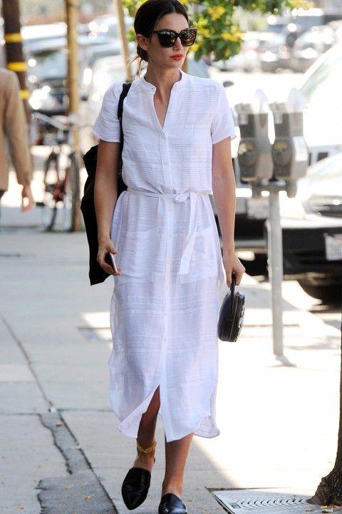 Еще один вариант - хлопковое легкое белое платье и черные кожаные туфли. Аутфит дополнен сумкой и очками.