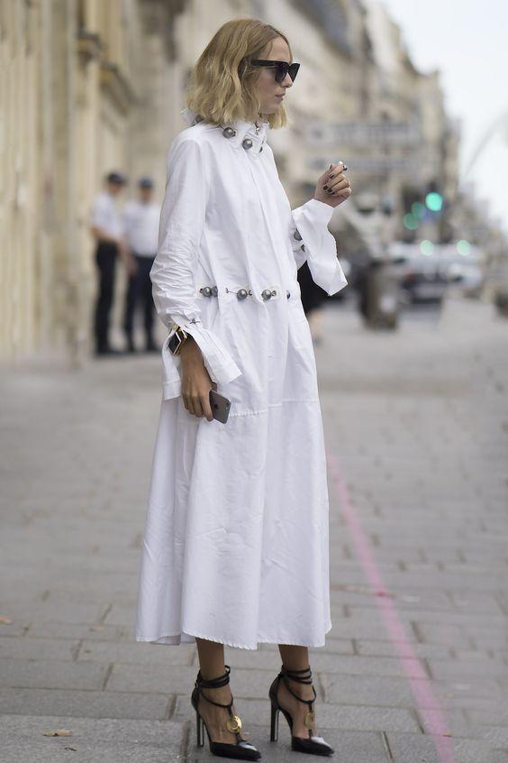 Белая длинная рубашка свободного кроя с металлическими пуговицами модно выглядит с черными лаковыми туфлями на высоком каблуке.
