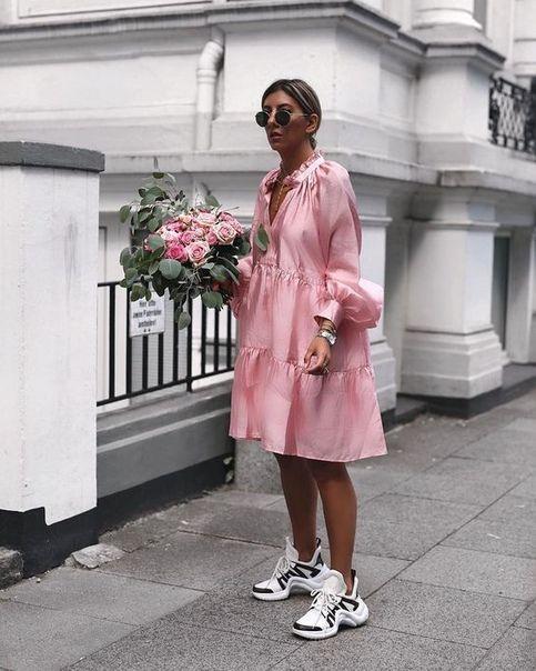 На фото объемное яркое платье длины миди в сочетании с массивными белыми кроссовками. Образ дополняют очки.