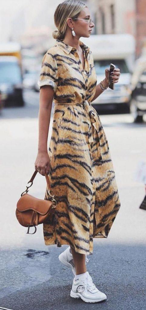 Леопардовое длинное платье-рубашка в сочетании с белыми кроссовками Chanel.