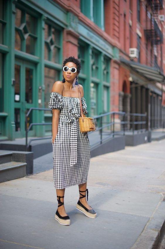 Клетчатое черно-белое платье ниже колена удачно выглядит с эспадрильями. Образ дополняет плетеная сумка через плечо.
