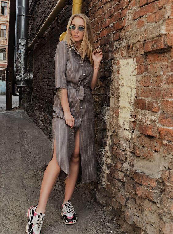Длинное платье-рубашка в полоску с поясом безупречно выглядит с массивными кроссовками. Образ дополнят очки.