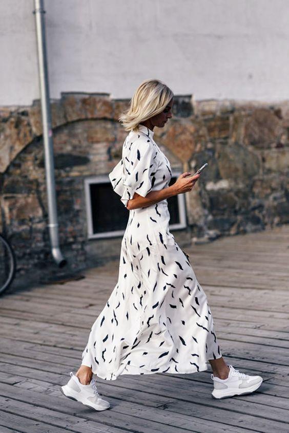 На девушке белое длинное платье с белыми кроссовками - идеальный вариант для прогулки.