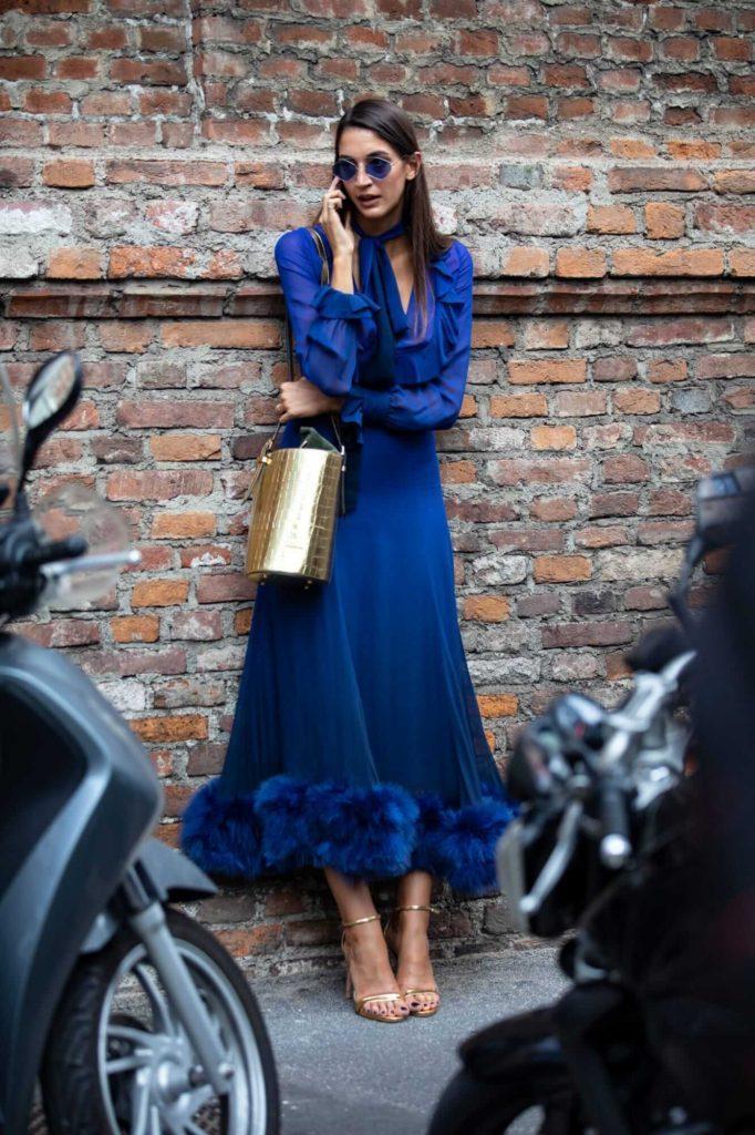 Синее платье с меховой окантовкой и золотистые босоножки создают единый гармоничный наряд.