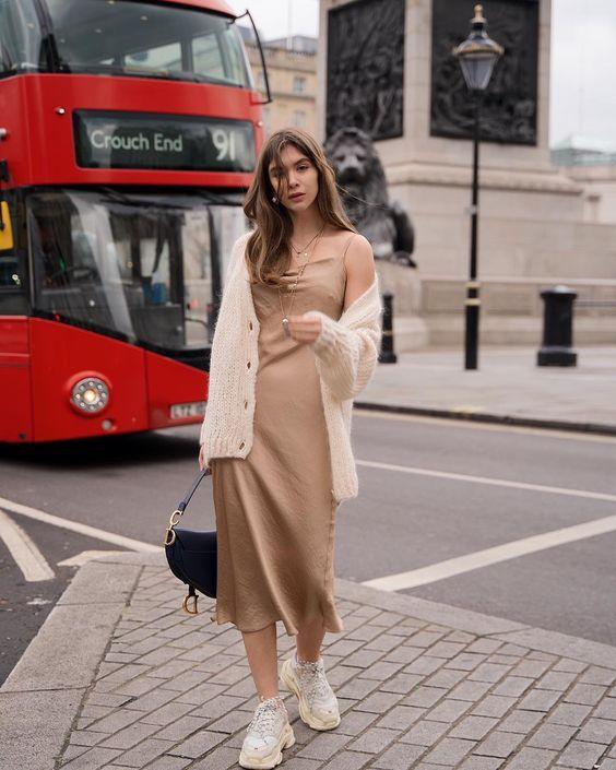Прямое нюдовое платье миди в сочетании с массивными белыми кроссовками. Образ дополнен вязаной кофтой и черной сумкой.