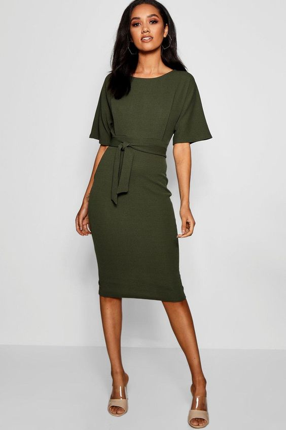 Платье-футляр с поясом цвета хаки сочетается с бежевыми босоножками с прозрачными вставками.