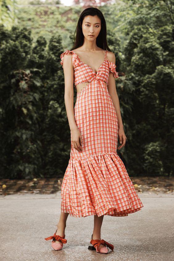 Клетчатое оранжевое платье с воланами и вырезами надето с нежно-розовыми балетками, украшенными оранжевыми бантами.