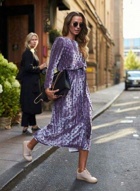 Яркое плисовое фиолетовое платье в горошек в сочетании с нежными нюдовыми кроссовками. Образ дополнен черной сумкой и очками.