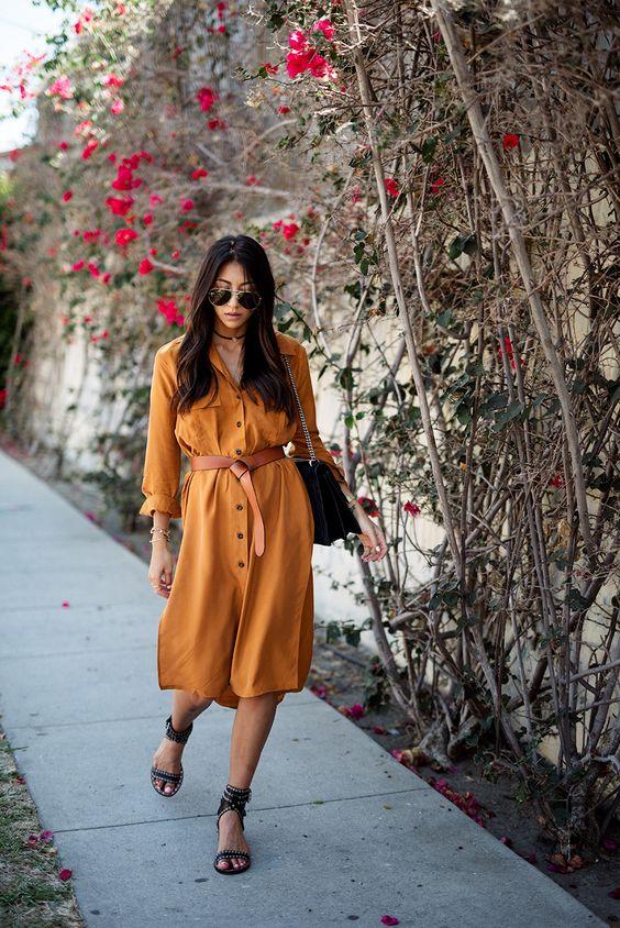 Горчичное платье миди с пуговицами и поясом в сочетании с черными босоножками. Образ дополнен поясной сумкой и солнцезащитными очками.